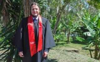 José Mario Carranza con una toga negra y un ribete rojo.