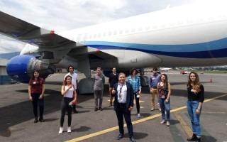 Grupo de estudiantes posando frente a un avión.
