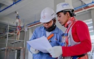 dos hombres en construcción sosteniendo plano