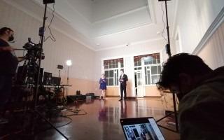 Imagen tras las cámaras de la transmisión en vivo. Se ven los presentadores, al fondo.