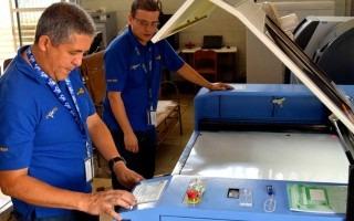 Imagen de dos hombres en una máquina para fabricar caretas protectoras.