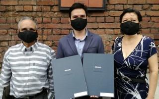 Jorge Mora Jara posa con sus padres y los dos diplomas que recibió.