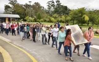 Imagen de funcionarios y estudiantes cargando una cruz y un cuadro con la imagen de la Virgen.