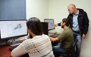 Los estudiantes ven las computadoras mientras el profesor les explica.