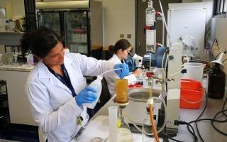 Imagen de dos estudiantes realizando un análisis químico.