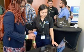 Una ingeniera pregunta a una estudiante, frente a una computadora.