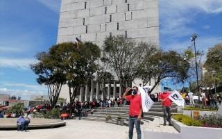 Personas manifestándose frente al edificio de la Asamblea Legislativa.