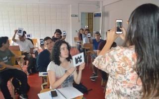 Imagen de una mujer que recoge la información con su celular y sus alumnos  están sentados con la respuesta en una hoja mostrándola hacia el frente.