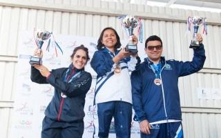 tres personas en un podio alzando los trofeos