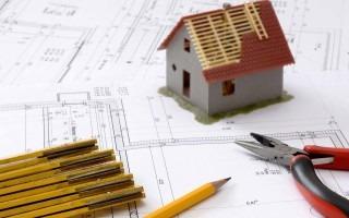 Imagen de un plano arquitectónico, una casa en miniatura y algunas herramientas