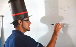 joven con sombrero de mago escribiendo en pizarra signos matemáticos