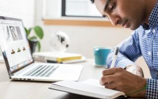 estudiante escribiendo junto a computadora