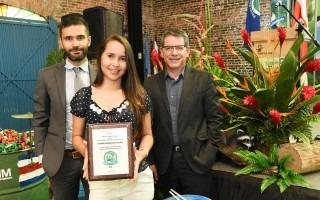 La regente ambiental sostiene el premio, acompañada del rector y el coordinador de la unidad de gestión ambiental.
