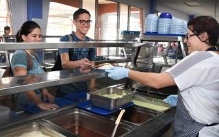 Dos estudiantes esperando que le sirvan almuerzo en el Restaurante Institucional del TEC.