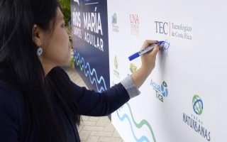 La integrante del Consejo Institucional, María Estrada, firma la manta representativa del Pacto.