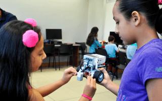 dos niñas con modelo robótico entre sus manos