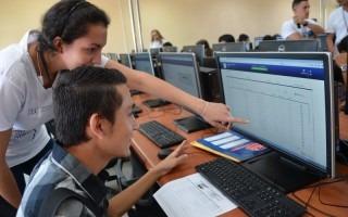 estudiantes frente a computadora señalando monitor