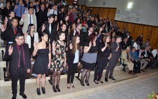 Estudiantes con la mano derecha levantada siendo juramentados.