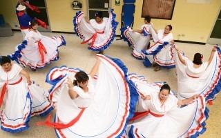 Un grupo de señoras baila con el vestido típico, de color blanco con ribetes azul y rojo.