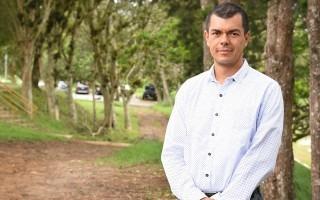 El Dr. Pérez, de pie, frente a unos árboles.