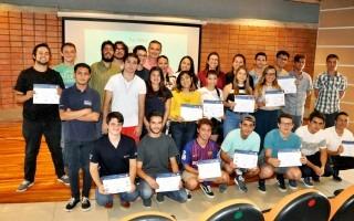 Unos 20 estudiantes muestran sus diplomas, posando junto a los profesores.