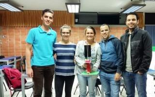 Cinco jóvenes: tres hombres y dos mujeres, posan para la foto, con la maqueta del Totem Inteligente.