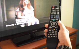 mano con control remoto y televisión