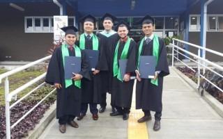 graduados con toga de pie posan con sus títulos