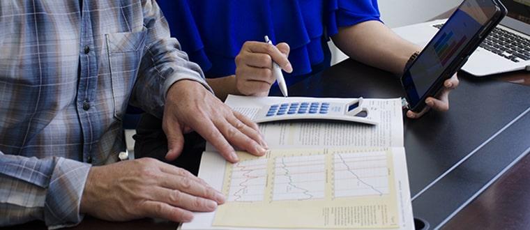 Dos personas en una mesa con una calculadora y computadora.