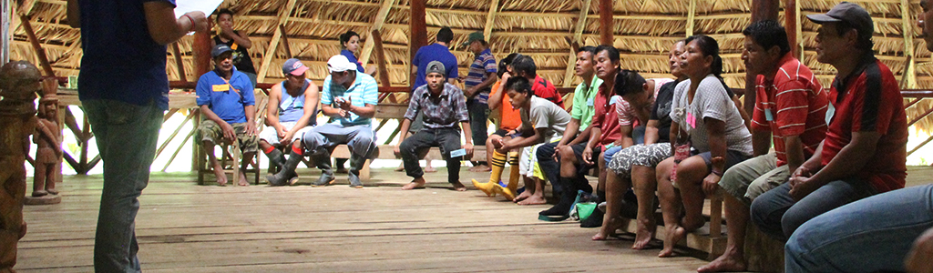 Indígenas reunidos en círculo