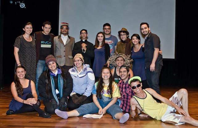Jóvenes con disfraces varios posan en el escenario.