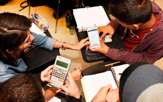 estudiantes utilizando calculadoras y teléfonos