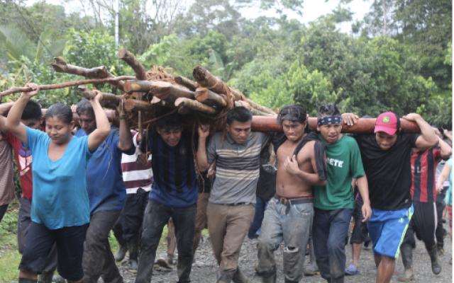 Grupo de indígenas cargando troncos de madera