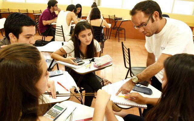 Imagen de un profesores explicándole matemáticas a cuatro estudiantes.
