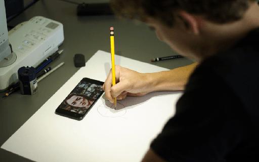 Un joven realiza un dibujo en la mesa.