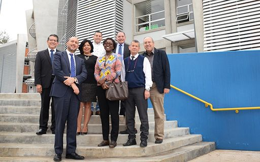 Authorities of the TEC and several officials of the World Bank pose in front of a new building.