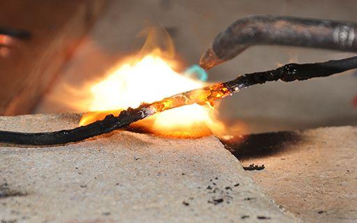 Un cable es quemado para comparar su estado después de que fue afectado por el fuego.