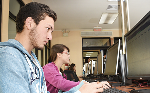 A young man in front of a computer.