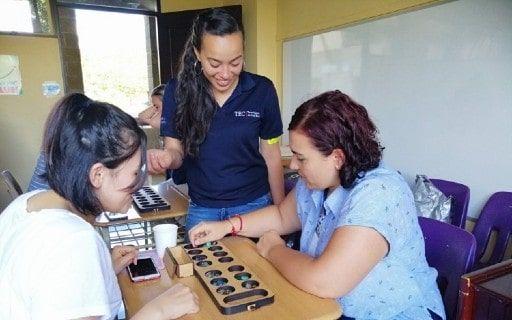 En la fotografía dos mujeres juegan, mientras aprenden matemática.