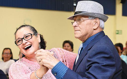 Una pareja de adultos mayores sonríe mientras baila.