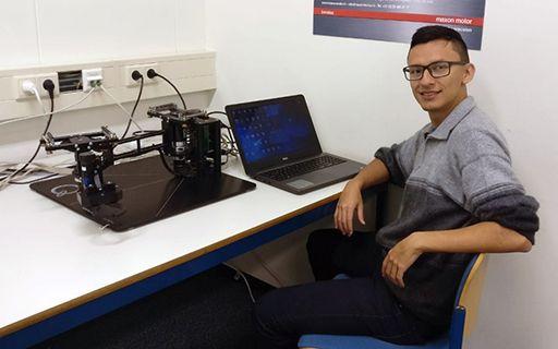 Juan Padilla junto a una computadora y un robot.